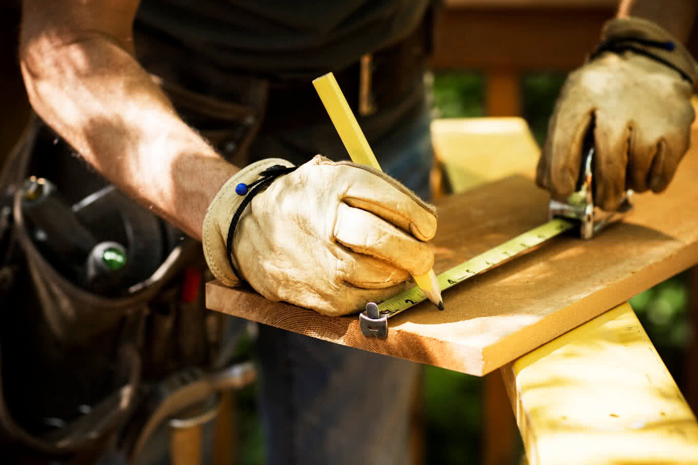Carpenter measuring a wooden plank at a construction site