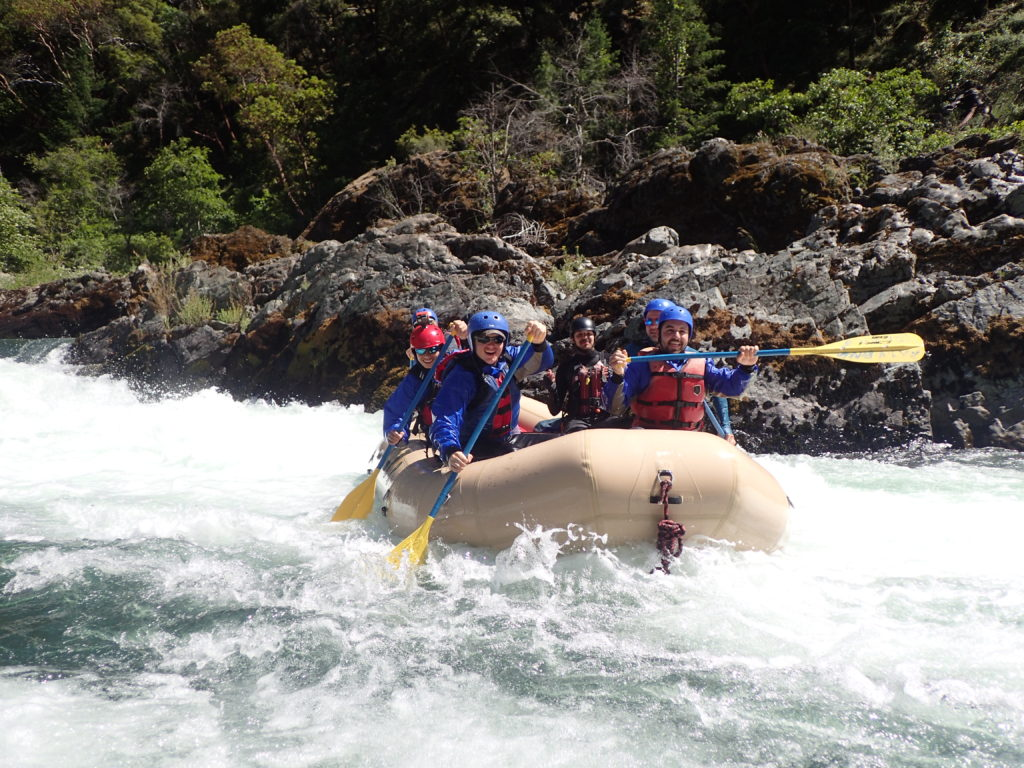 Guide School students in a tan colored raft successfully complete a rapid on the Trinity River..