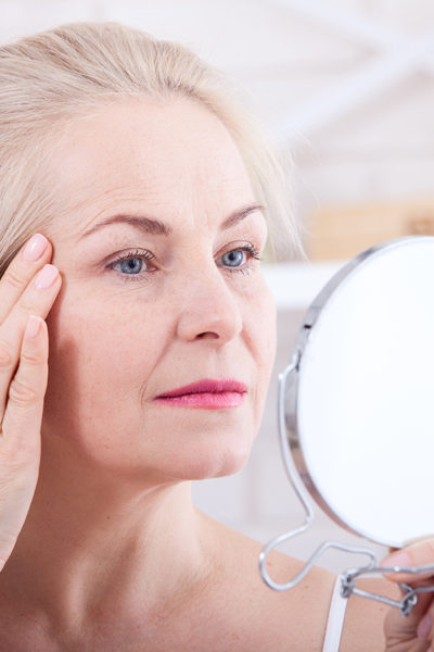 Forty years old woman looking at wrinkles in mirror. Plastic surgery and collagen injections. Makeup. Macro face. Selective focus on the face