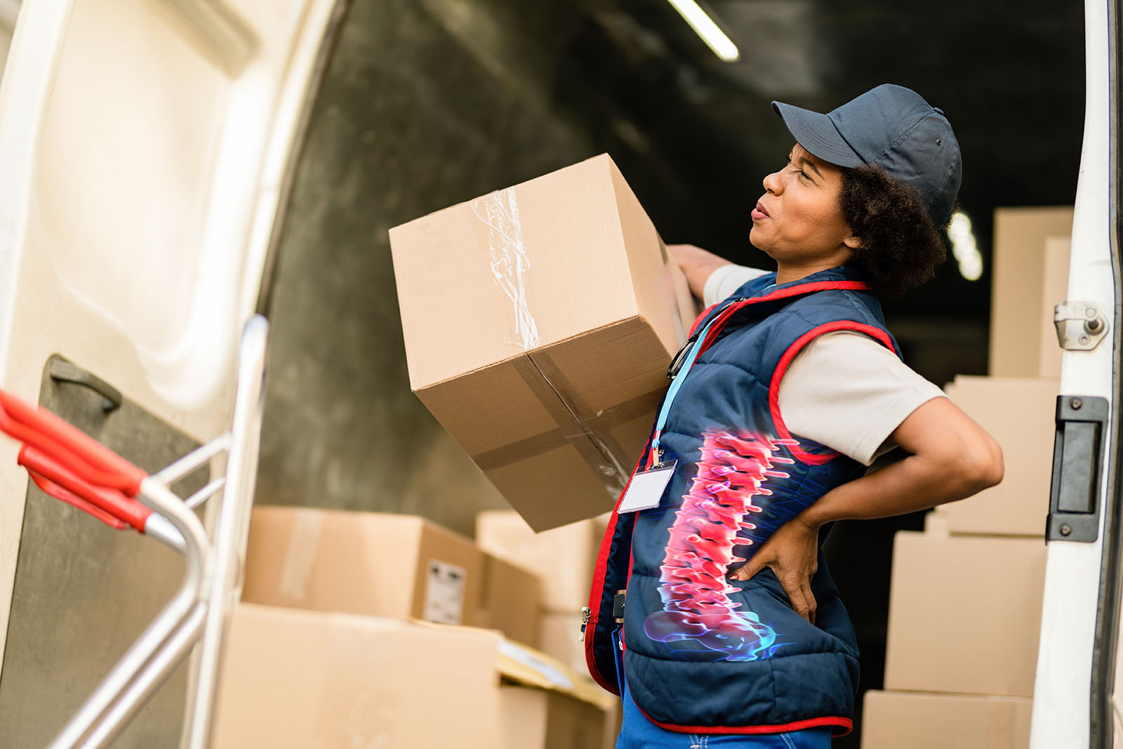 Black female courier experiencing pain in lower back while unloading packages from a mini van.