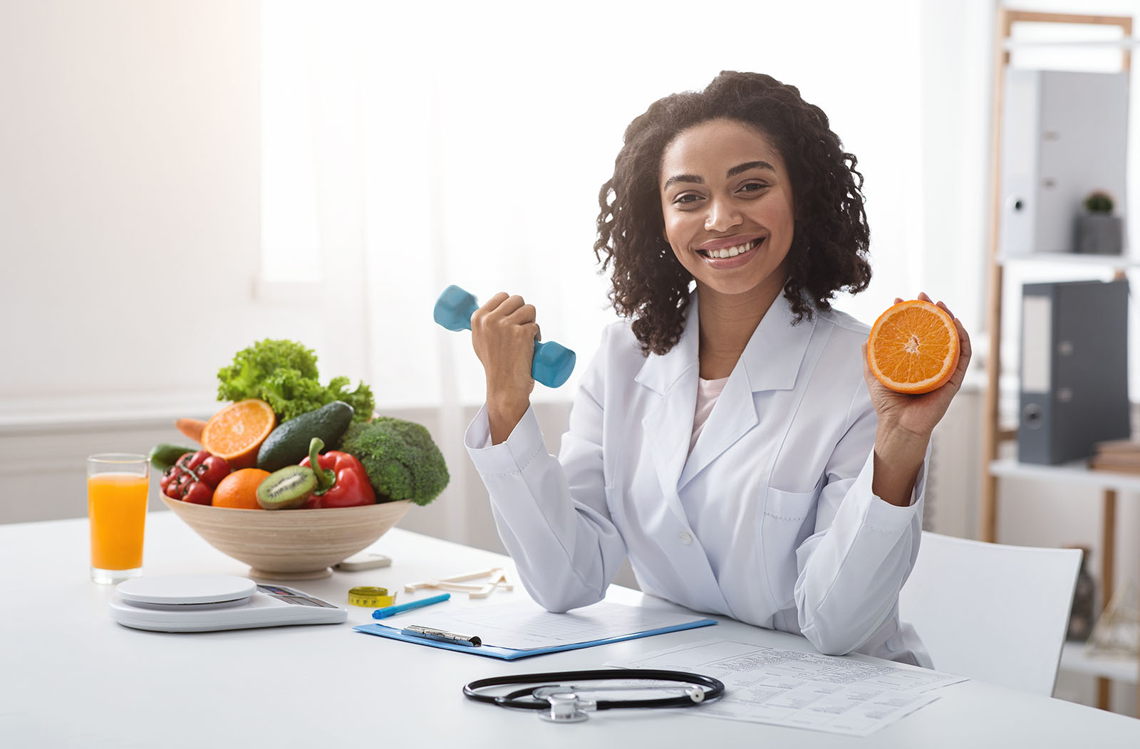 Sport and vitamins for immunity. Happy black woman doctor holding orange and barbell in clinic, posing at her workplace, free space