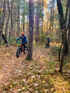 Riding bike in the woods during the Fall is a great way for couples to re-connect.