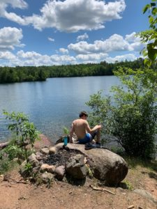 Our camp outs take folks to idyllic spots, this one is a Summer Northwoods lake view of a teenager sitting on a boulder in the sun looking out.