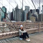 Girl in her thirties loving the Brooklyn Bridge with the Manhattan skyline behind her sitting on the bridge in a hat