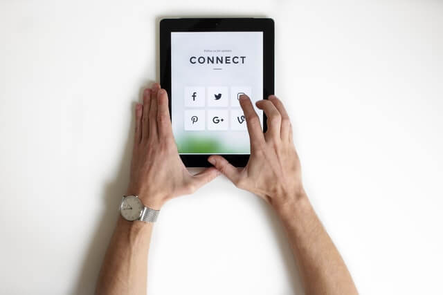 Hands using a tablet computer for small business digital marketing