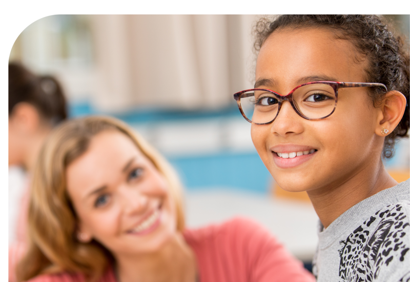 A young girl with glasses smiling with her teacher
