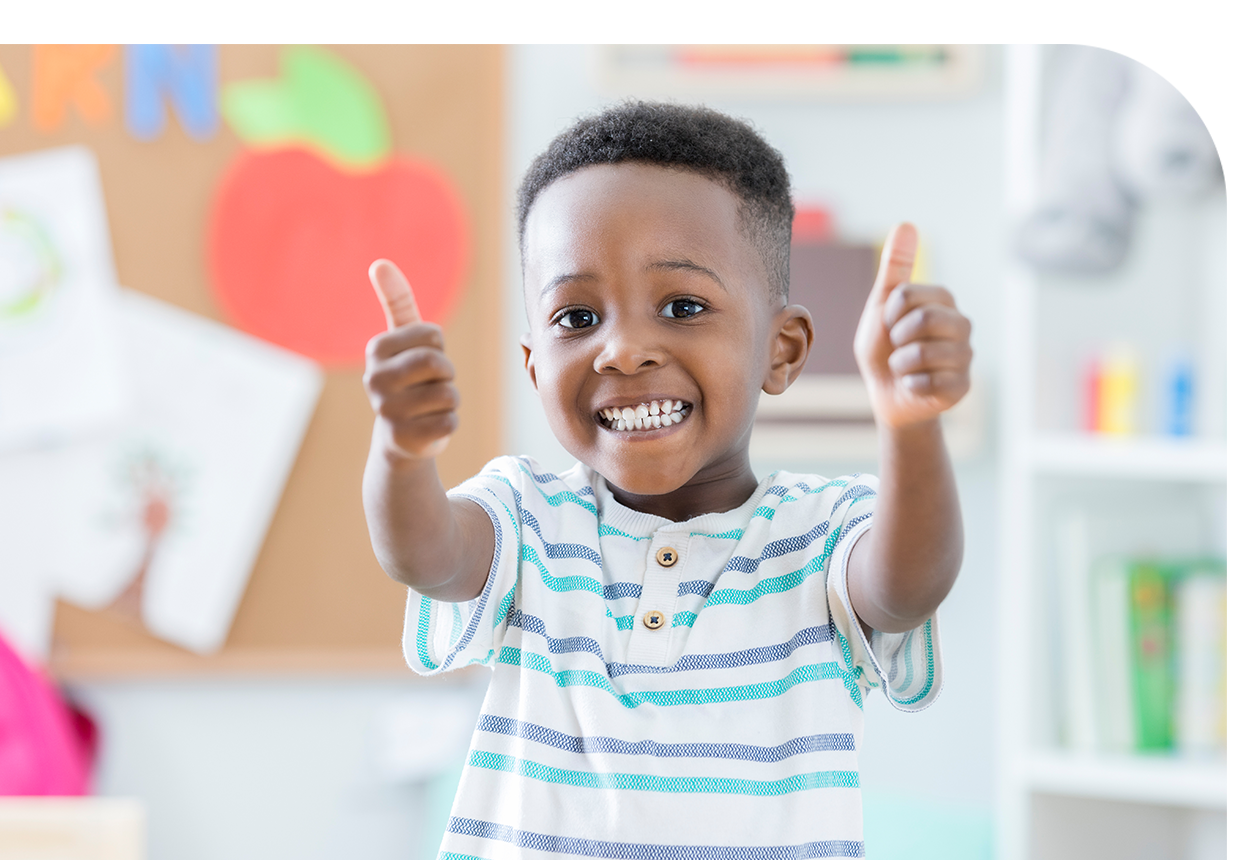 A young boy giving a thumbs up