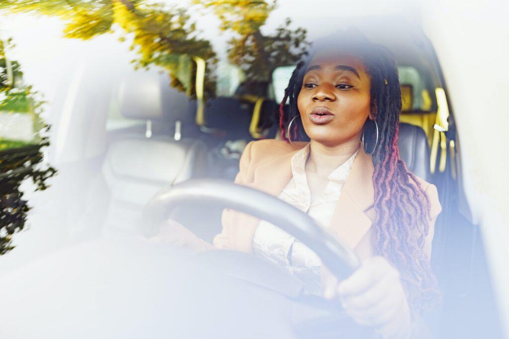 Emotional black woman sitting in a car