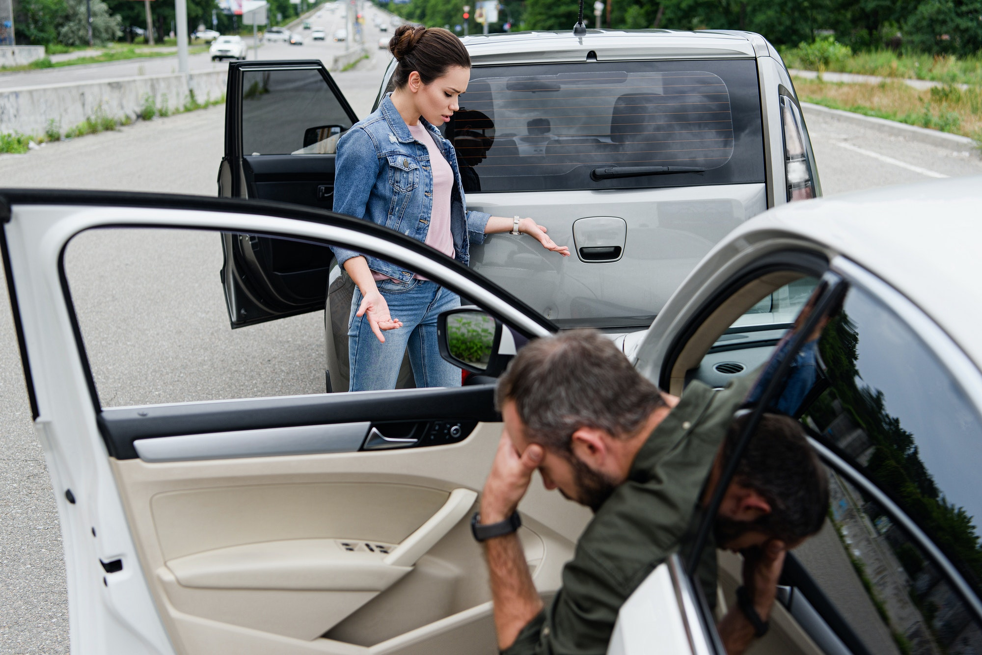 female driver looking at cars after car accident on road
