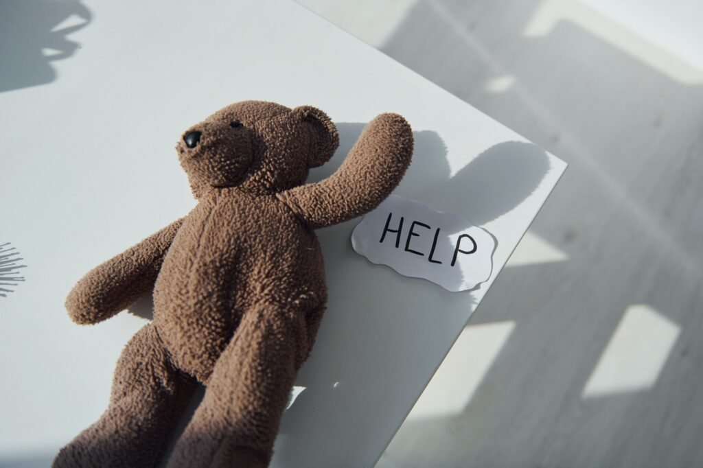 Teddy bear toy lying down on the table. Conception of domestic violence