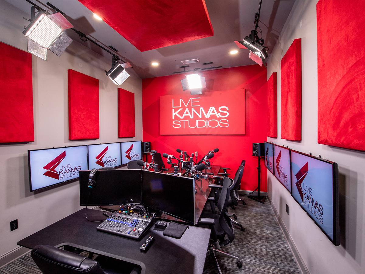 A bright red room with microphones at a table, decorated with Live Kanvas Studios branding
