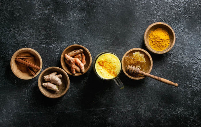 Glass of ayurvedic drink golden milk turmeric latte with curcuma powder and ingredients in wooden bowls above over black texture background. Top view, space