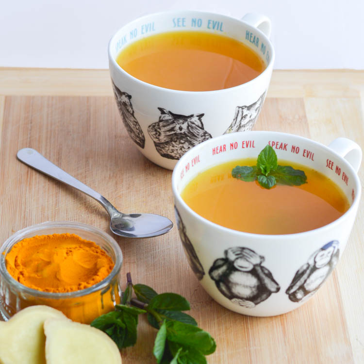 ginger turmeric tea in a white cup mint herbal