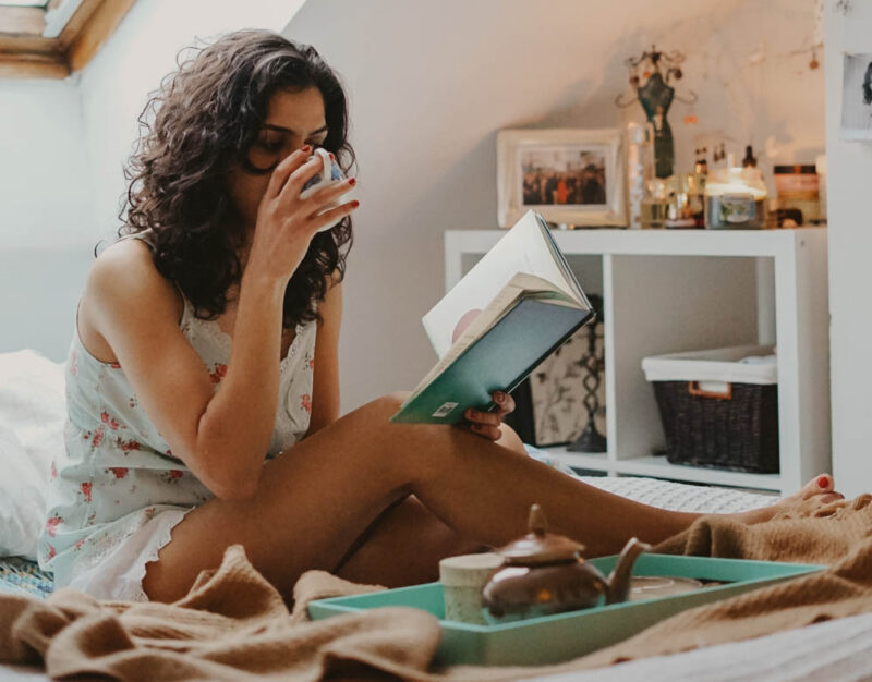 woman drinking tea in bed