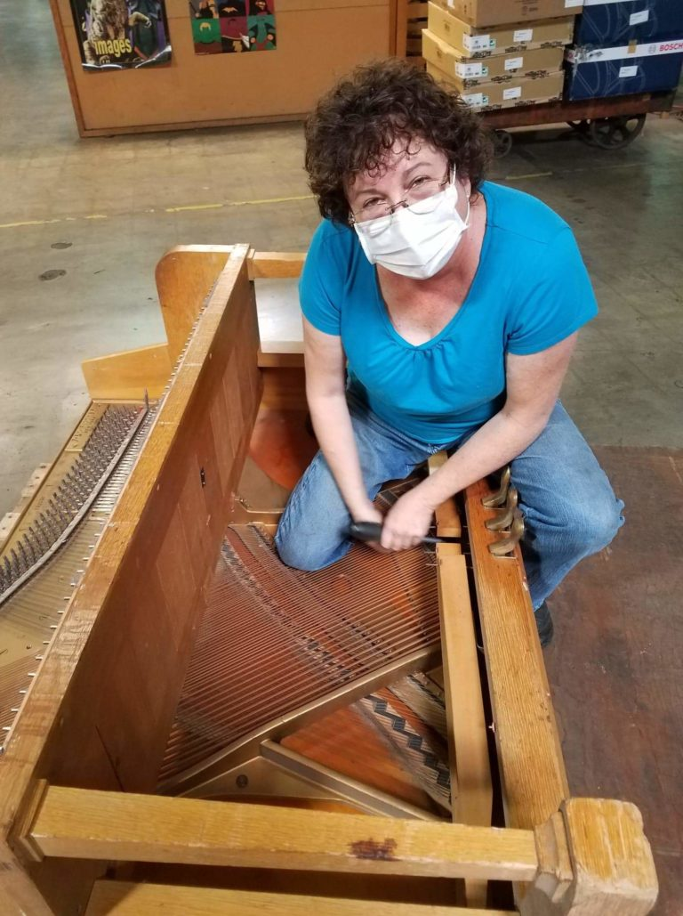 Dismantling a worn out piano for the school district.