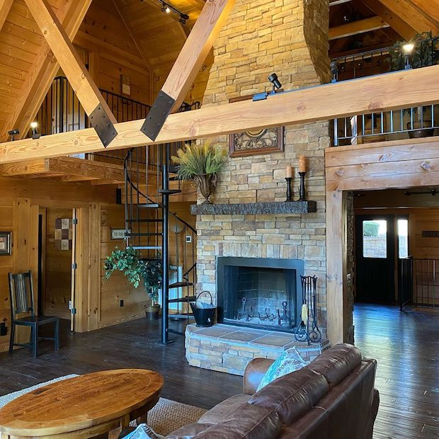 photo of great room of timberframe home with exposed wood ceiling and A-Frame trusses in second story roof area