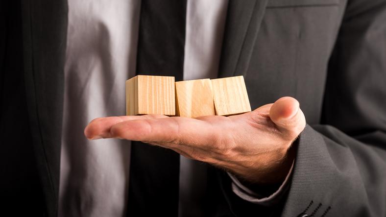 Businessman holding three blank wooden cubes