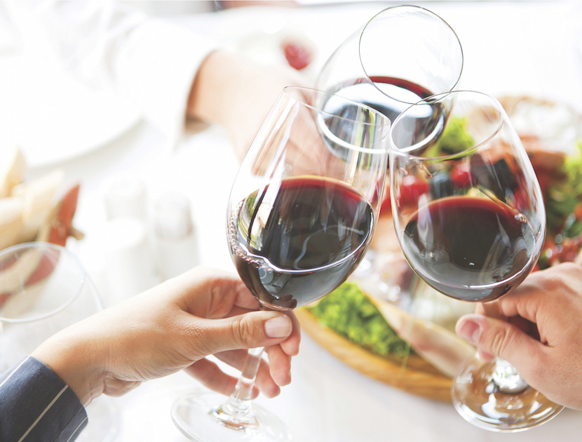 A bright and warm image of wine-filled glasses held aloft in a toast.