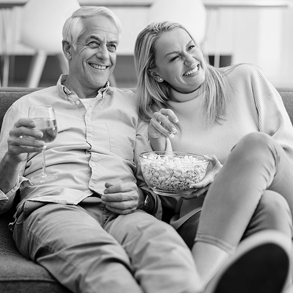 A couple eating popcorn on the couch