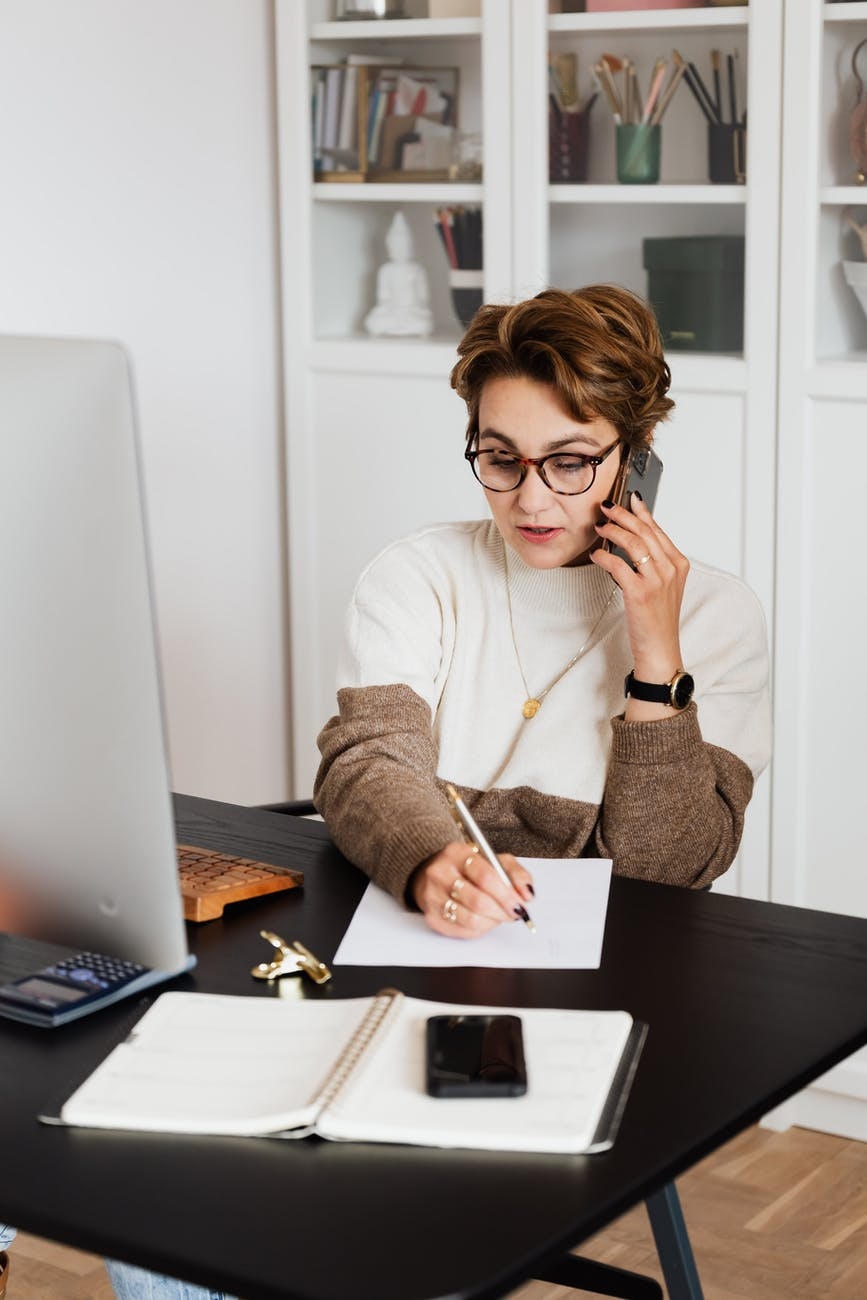 remote employee talking on phone and taking notes
