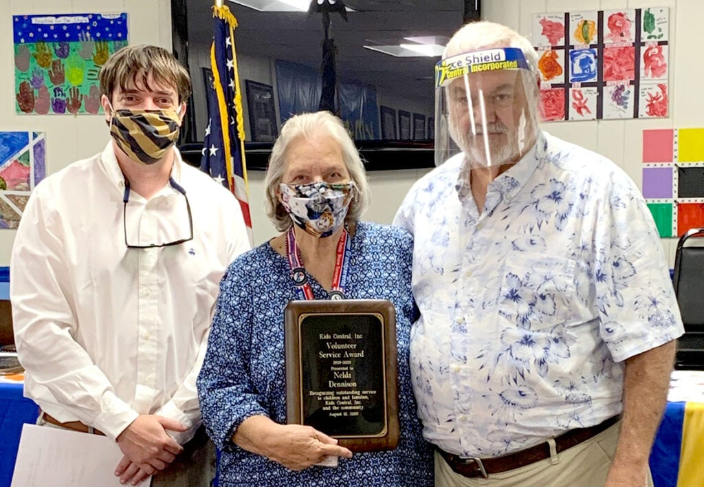 MEOC foster grandparent Nelda 'Moe' Dennison (center) is this year's recipient of Kids Central Inc.'s Volunteer of the Year Award. Presenting the award at Kids Central's August board meeting is chairman Will Sturgill (left) and executive director Darrell Edwards.