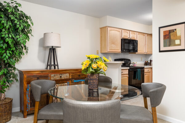 A dining room with a kitchen view at Chesterfield Village Apartments