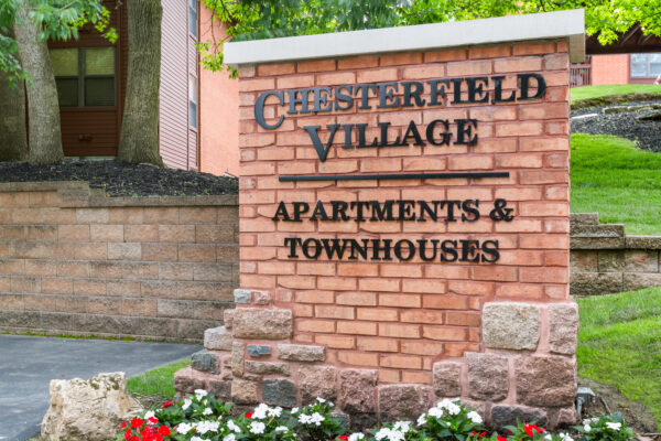 A close up of a brick sign of The Chesterfield Village Apartments