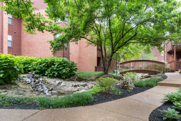 A pathway along water with a bridge at Chesterfield Village Apartments
