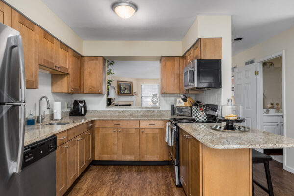 A marble kitchen countertop with a view of the bathroom and living room at Chesterfield Village Apartments
