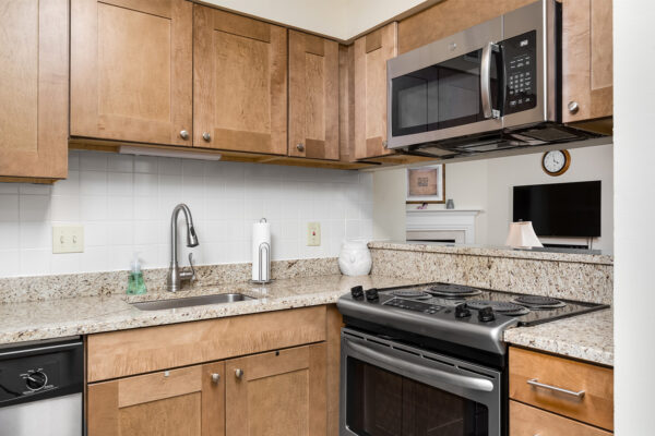A marble kitchen countertop with stainless steel appliances at Chesterfield Village Apartments
