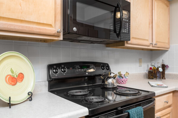 A stovetop and microwave at Chesterfield Village Apartments