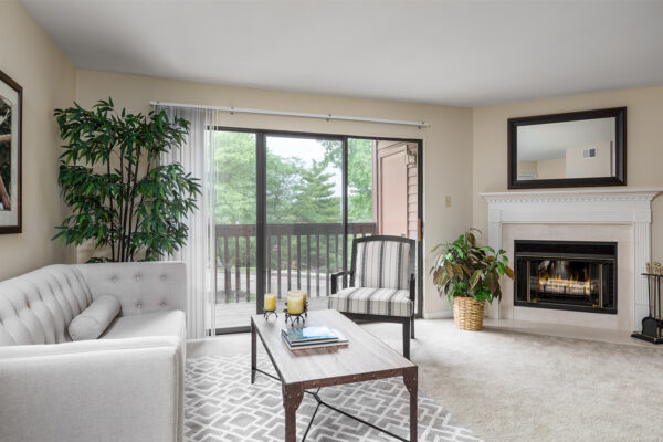 A living room and fireplace at Chesterfield Village Apartments