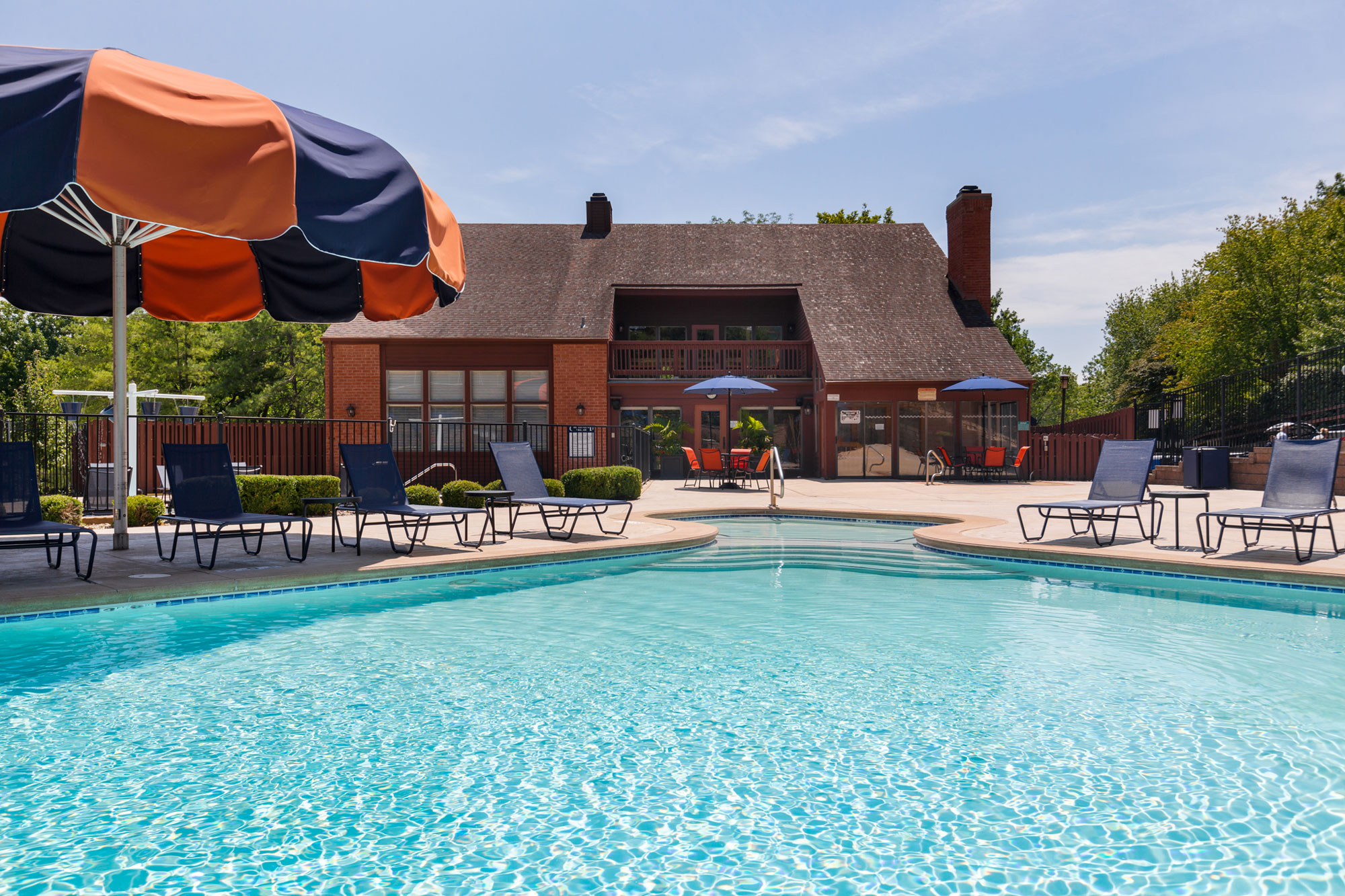 The Chesterfield Village Apartments clubhouse with a foreground of the swimming pool