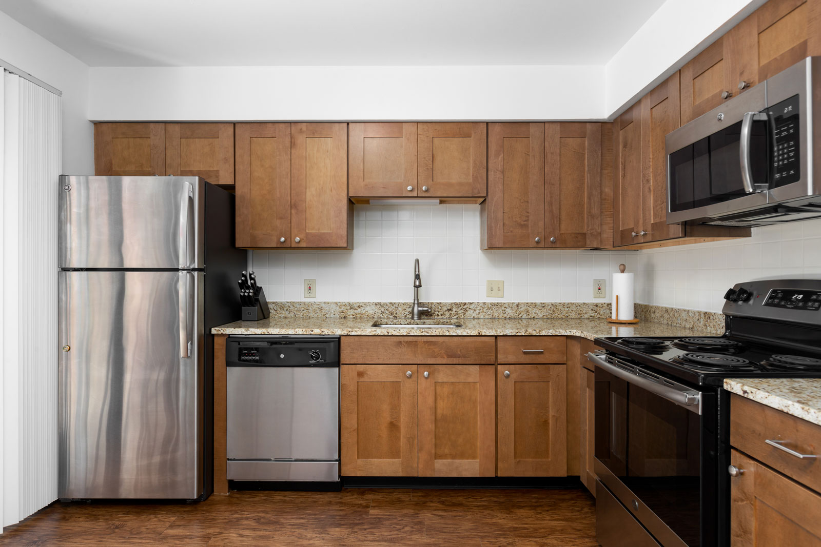 A kitchen with cabinets and stainless steel appliances at Chesterfield Village Apartments