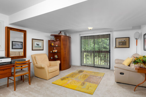 A basement living room with a recliner and sofa at Chesterfield Village Apartments