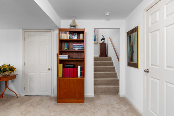 A basement living room with stairs leading up at Chesterfield Village Apartments