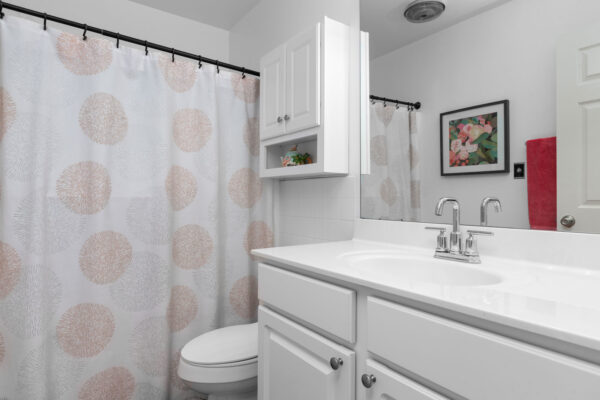 A bathroom with a drawn shower curtain in the background at Chesterfield Village Apartments