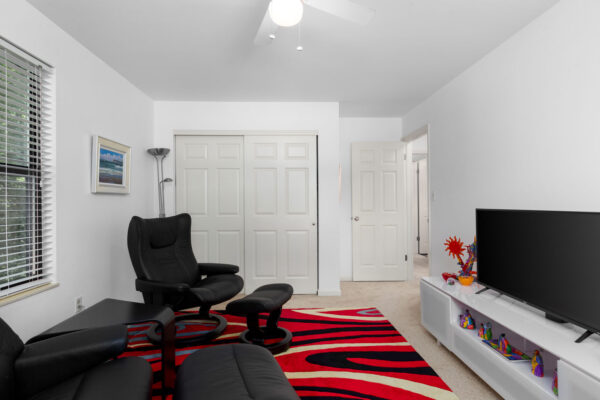 a room with chairs and a television at Chesterfield Village Apartments
