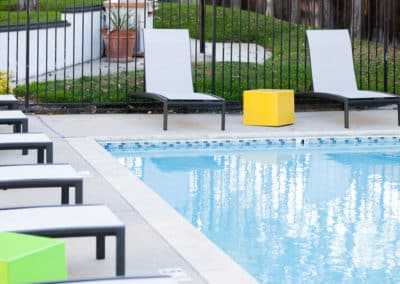 Pool with white chairs at Eastside Apartments