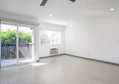 Empty living room with dual pane windows and natural light leading to the balcony