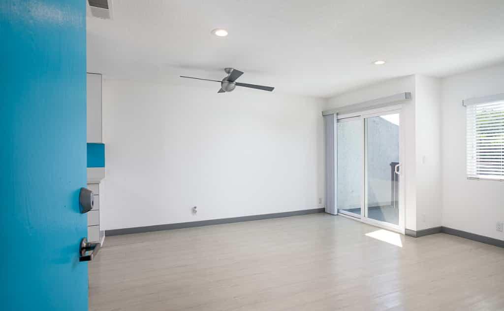 Open door into bedroom space with ceiling fan
