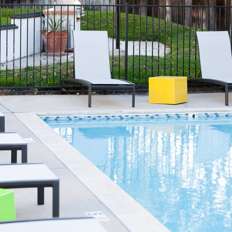 Swimming Pool with White Poolside Chairs