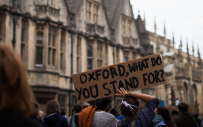 Oxford BLM Protest Image featuring a person holding a sign that reads 'Oxford, What do you stand for?' by Emily Jarrett Photography
