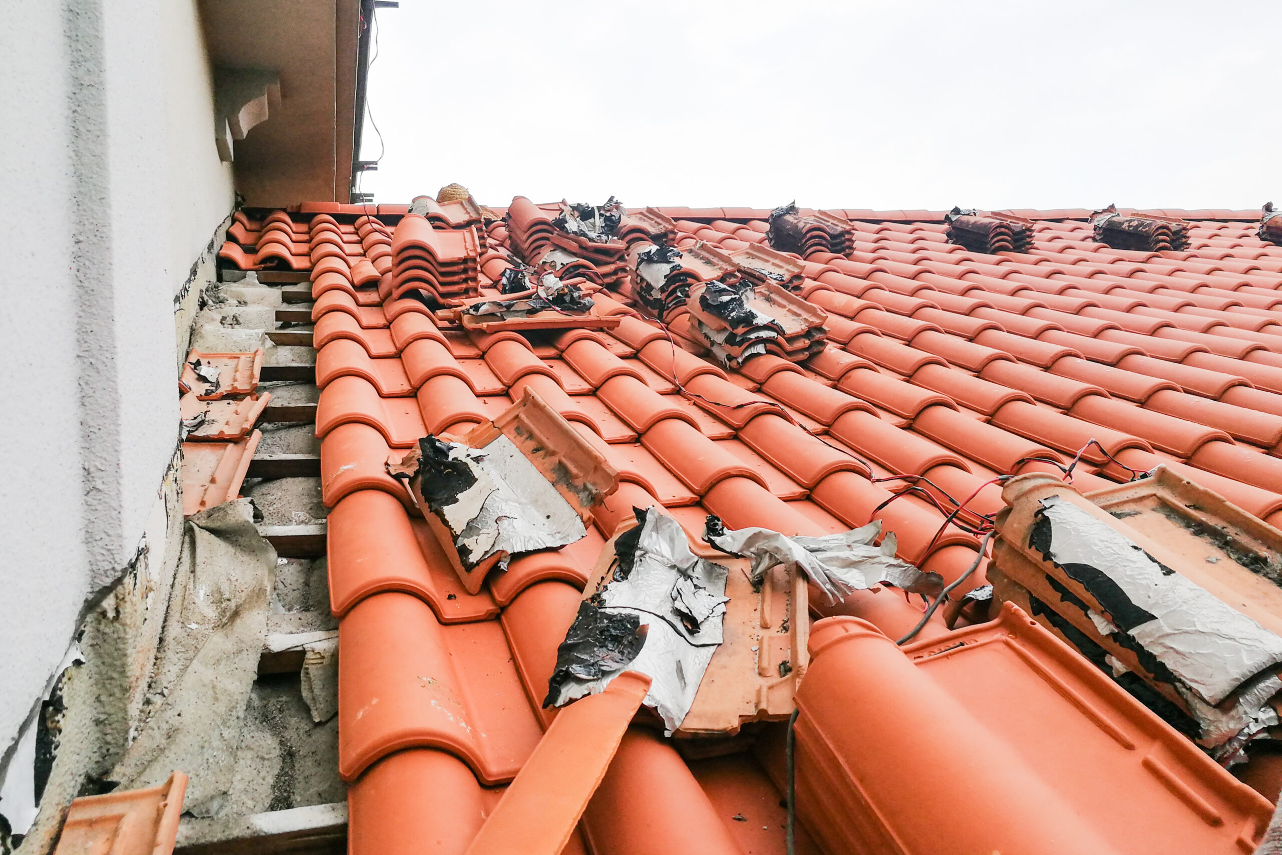 Old moldy roof tile being replaced with new tiles with nobody