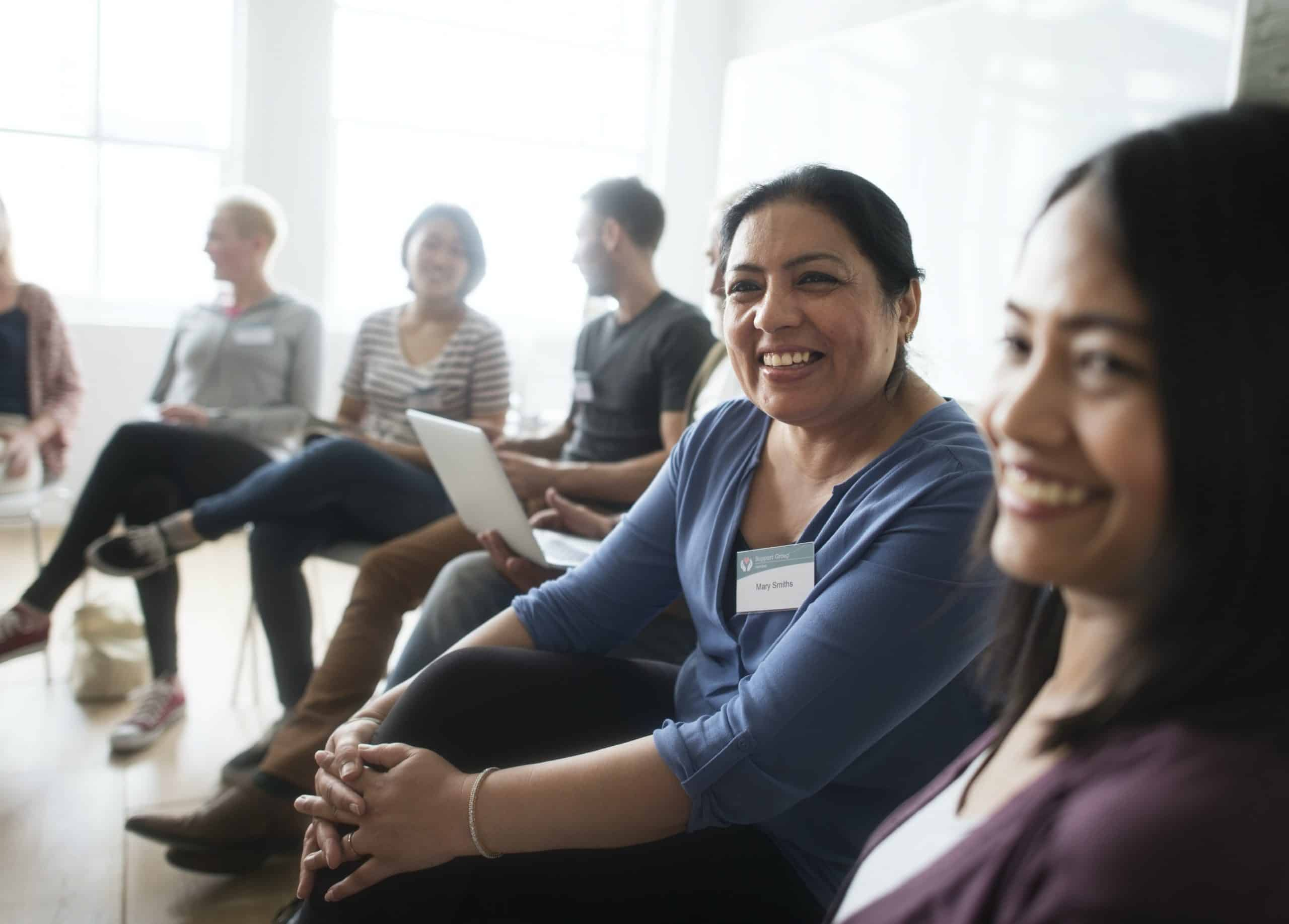Smiling group participants sit on chairs in a semi-circle