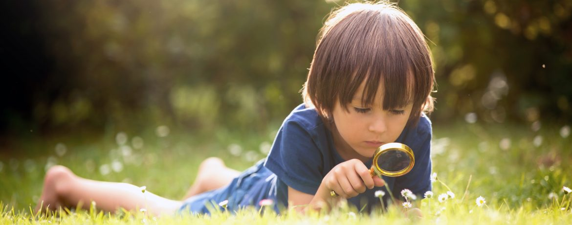 Curious child looking through magnifying glass at grass