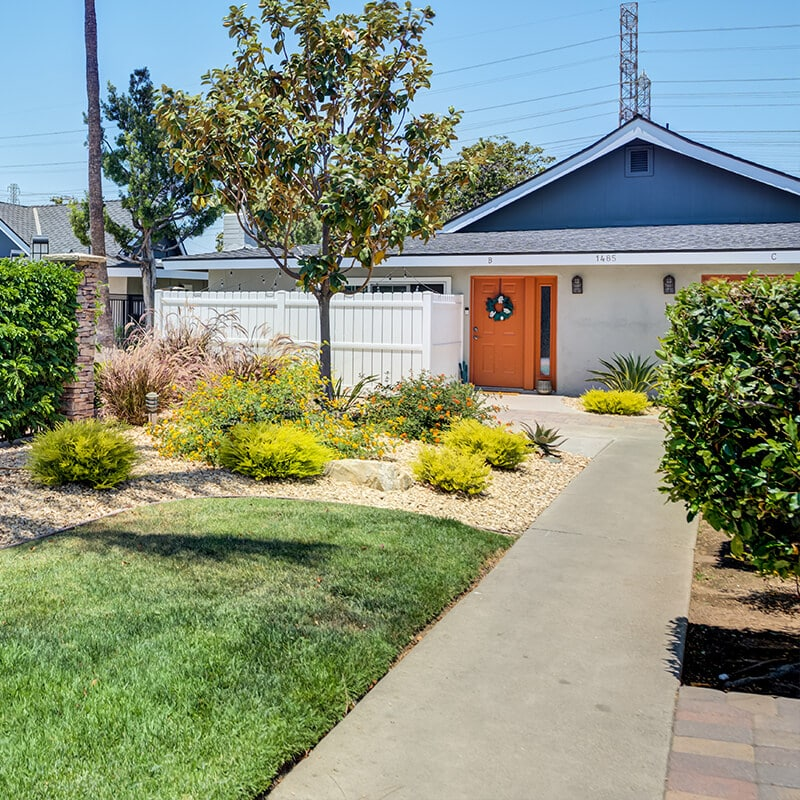 Path leading to apartment community with green grass and landscaping