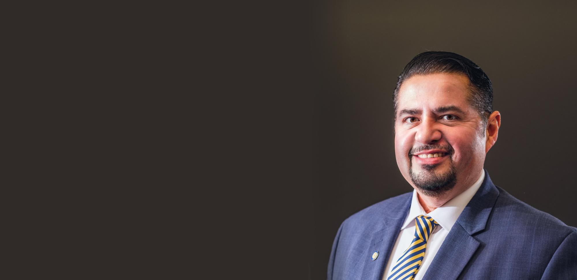 Attorney Joe Flores smiling wearing suite