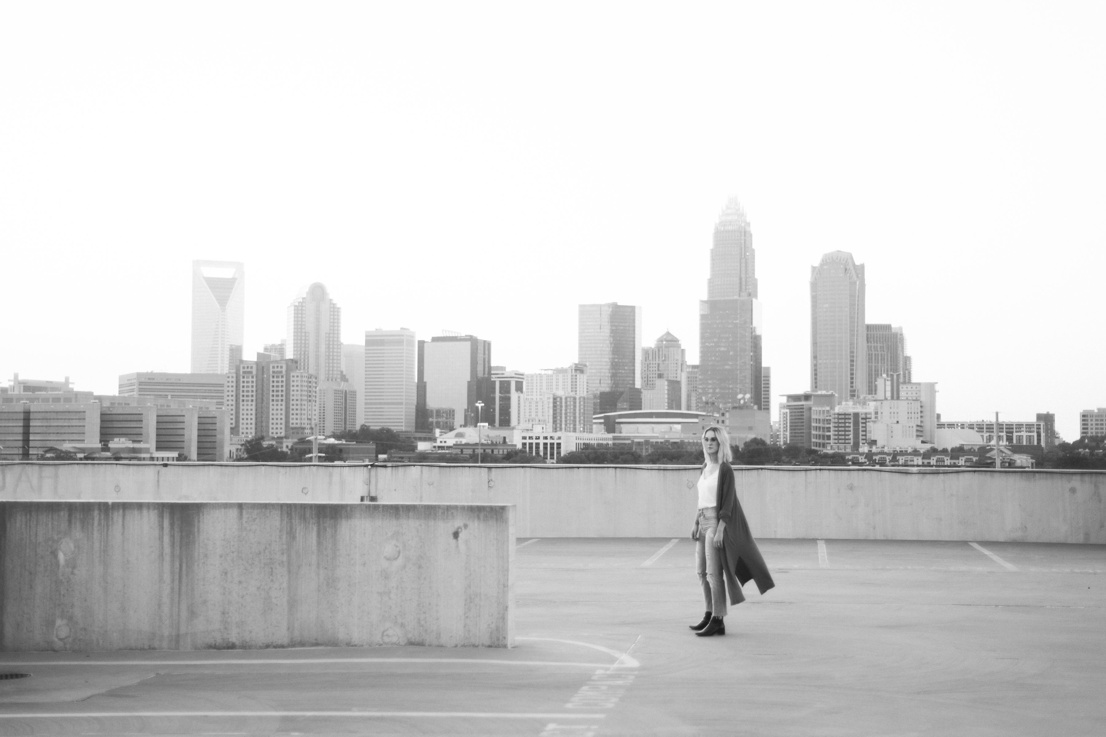 Girl standing on rooftop overlooking uptown Charlotte North Carolina