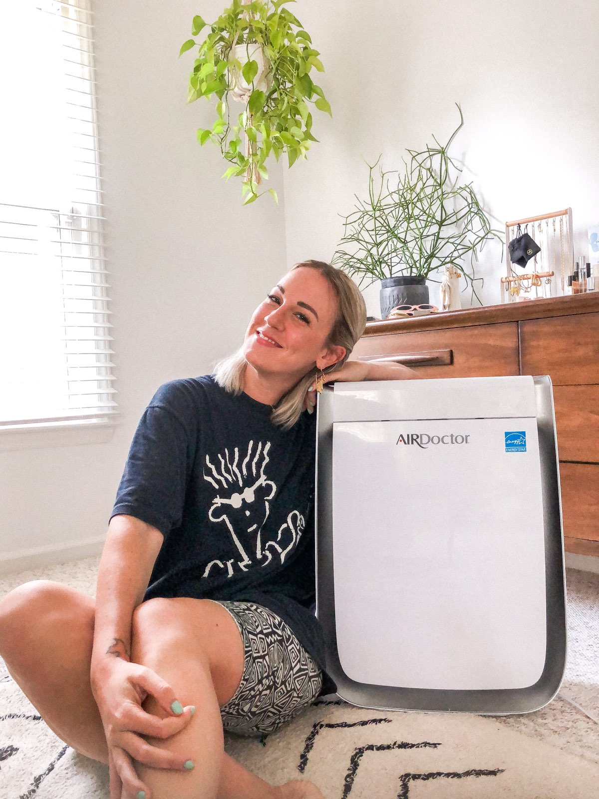 Girl sitting with an air purifier. AirDoctor Pro Air Purifier